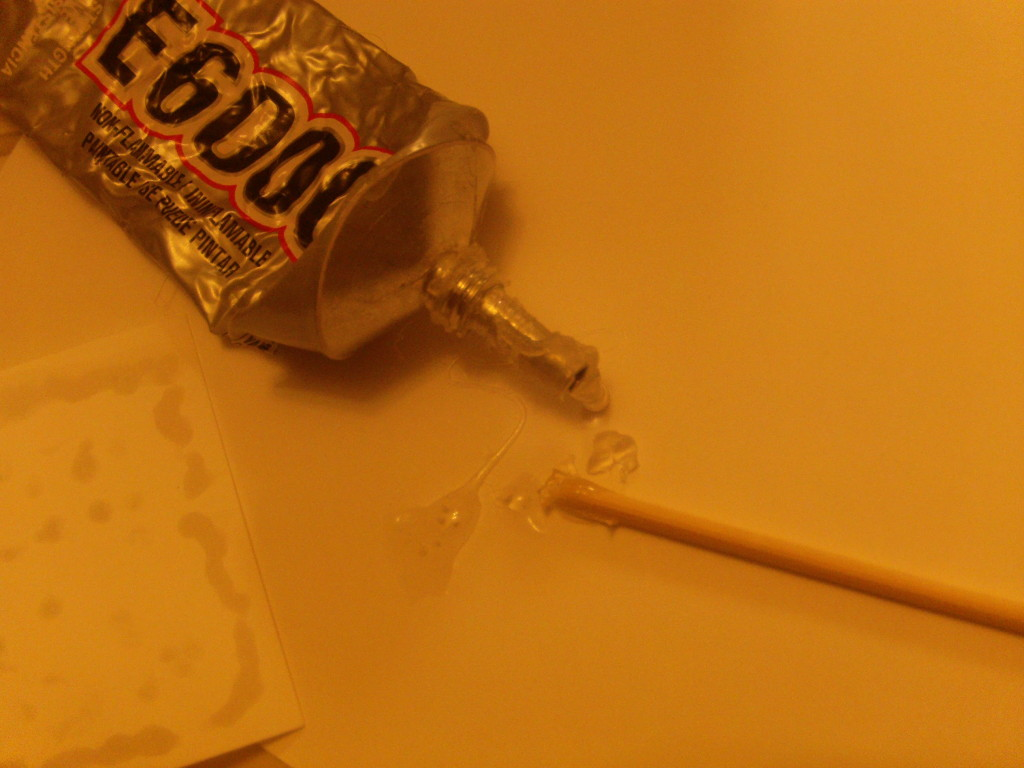 Now this is where your glue comes in. E6000 is handy because it works like a hot glue gun would, but the glue stays liquid longer and it doesn't require heat. Squeeze some out like paint onto a sheet of your cardstock and use your skewer to apply it to a side of one of your new corners
